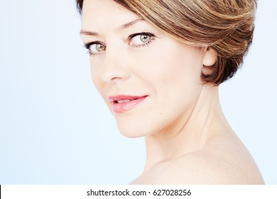 Face close up of beautiful middle aged woman with short brown hair, red lips and fresh makeup over blue background - beauty concept