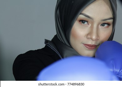 Face close up muslim woman wearing boxing gloves. Cancer Fighter Woman power Survival Concept.