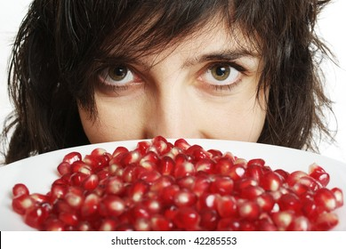 Face closeup of beautiful woman holds pomegranate berries in white plate, isolated on white