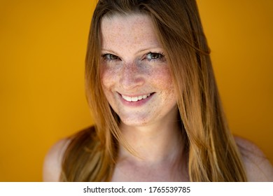 Face closeup of smiling european woman looking to camera. Likeable long-haired lady over yellow background. Image.