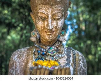 face closeup of a stone statue in asia with nature background