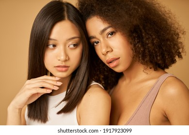 Face closeup of two beautiful mixed race young women with perfect skin posing for camera while standing isolated over beige background