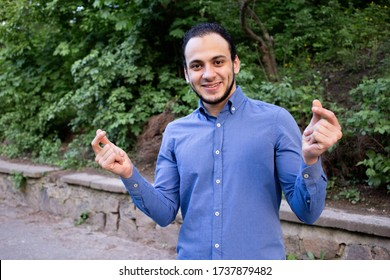 Face closeup of the young smiling man from Middle Eastern who puts his fingers together and makes finger click. Closeup portrait of a man from Egypt in blue shirt in the park.