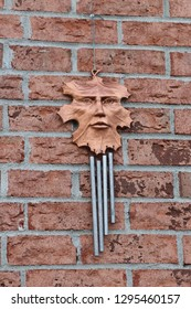 Face in copper  leaf wind chime hanging on red orange brick wall-abstract
