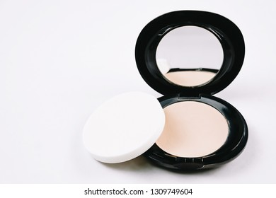 face cosmetic compact makeup powder in black round plastic case with mirror and sponge isolated on white background
