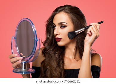 Face Cosmetic. Young woman with mirror and makeup brush.