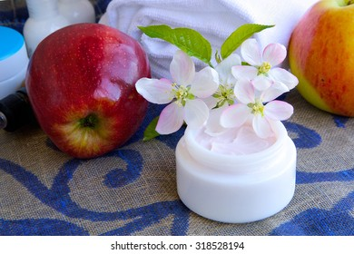 Face cream with apple blossoms extract.Apples,dropper bottle,white towels in the background.