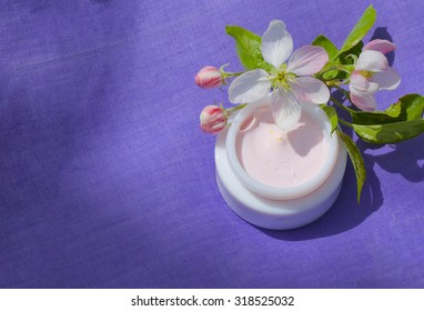 Face cream with apple tree blossoms extract on a violet surface.