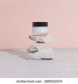 Face cream on top of stacked rocks. Clean and minimal cosmetics or beauty concept.