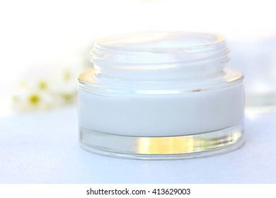 Face cream on white wooden table with shallow depth of field.