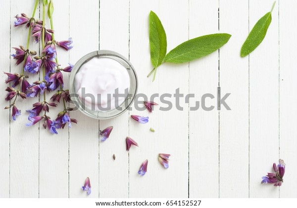 face cream with sage herbal flowers on white wooden table background