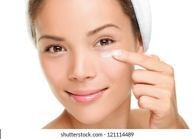 Face cream woman applying skin cream under eyes. Beauty eye contour wrinkle cream or anti-aging skin care cream. Beautiful young mixed race Asian  / Caucasian beauty model isolated on white background