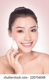 Face cream woman applying skin cream. young woman closeup applying foundation. Beautiful young asian beauty model isolated on white background