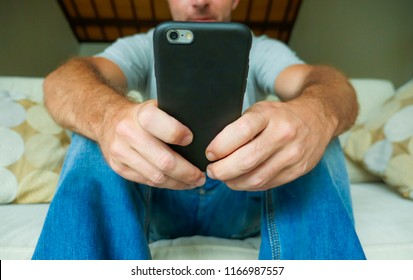face crop lifestyle portrait with close up hands of young happy man holding mobile phone sitting relaxed at home couch using internet social media app on smartphone networking and texting