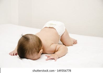 Face down lying baby on bed.