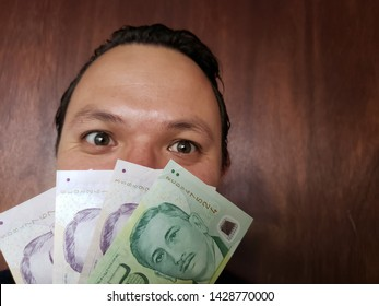 face with emotion expression of a young man with singaporean banknotes