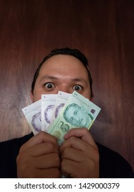 face with emotion expression of a young man and holding Singaporean banknotes