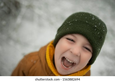 the face of emotional boy in a yellow down jacket and green hat catches snowflakes on a winter day