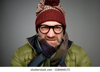 Face of european angry and furious male in warm clothes and glasses on a gray background. He does not like cold weather in winter