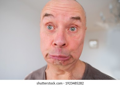 face of a European old man close up, wrinkles on the aging skin, bares teeth, makes grimaces, the concept of mental health, cosmetology, age-related changes