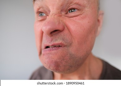 face of a European old man close-up, wrinkles on the aging skin, bares his teeth, makes grimaces, opening his mouth, the concept of mental health, cosmetology, age-related changes