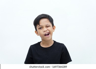 Face expression concept. Asian boy playing funny face over white background