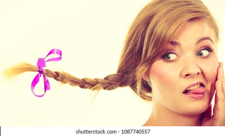 Face expression, fooling around concept. Teenage girl in blonde braid windblown hair making funny, silly faces.