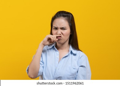 Face expression of human.  Asian female smelling disgusted odor and pinching his nose in studio shoot yellow background.