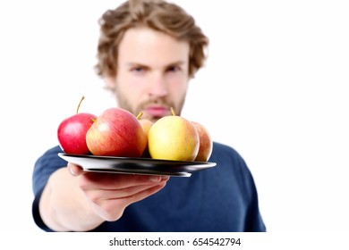 Face expression of strong and confident man offering plate full of apples. Isolated on white background, selective focus. Concept of offer and trick
