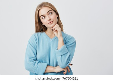 Face expressions and emotions. Thoughtful young pretty girl in blue sweater holding hand under her head, having doubtful look while can't decide what clothes to wear on friend's birthday party