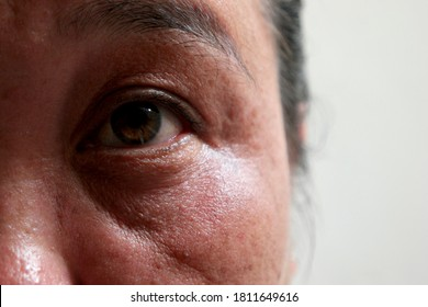 Face and eyes,45s Asian woman.Her brown eyes filled up with tears.Depression,stress in postmenopausal women or menopause or Middle-aged.Hormonal changes cause her to regret or cry.Selective focus.
