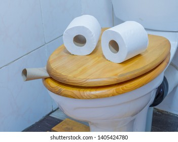 A face formed by two rolls of paper placed on top of a closed toilet lid image with copy space in landscape format