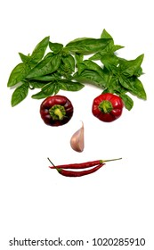 Face of fresh vegetables and greens, on white background. Vegetative face. Healthy vegetarian cuisine. View from above.
