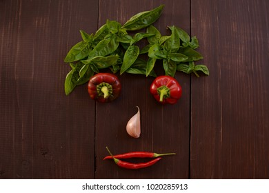 Face of fresh vegetables and greens, on a wooden background. Vegetative face. Healthy vegetarian cuisine. View from above