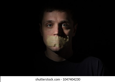 Face of a frightened man with a mouth taped violently with his mouth isolated on a black background