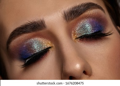 Face of a girl with luxury makeup and perfect skin. She has closed her eyes. Blue and golden eyeshadow, false eyelashes and brown eyebrows. Close up