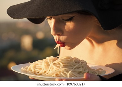 Face girl for magazine cover. Girl face portrait in your advertisnent. restaurant critic tatse italian pasta. restaurant, woman with red lips in black hat eating pasta.