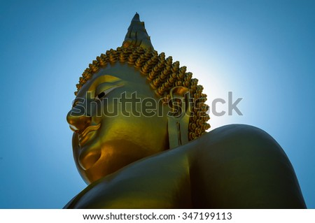 017d0006eef62 Face of Golden Buddha statue with sunlight like halo radiant on head with  blue background