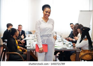 Face of handsome african american business woman, holding tablet on the background of business peoples multiracial team meeting, sitting in office table.