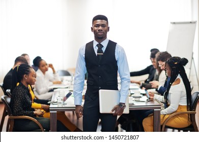 Face of handsome african business man, holding laptop on the background of business peoples multiracial team meeting, sitting in office table.
