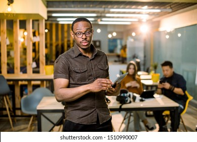 Face of handsome african business man, holding tablet on the background of business peoples multiracial team meeting, sitting in office table