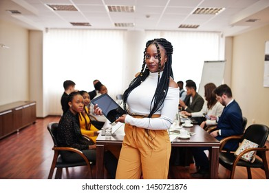 Face of handsome african business woman, holding tablet on the background of business peoples multiracial team meeting, sitting in office table.