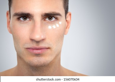 Face of handsome young man with moisturizer applied under his eyes.