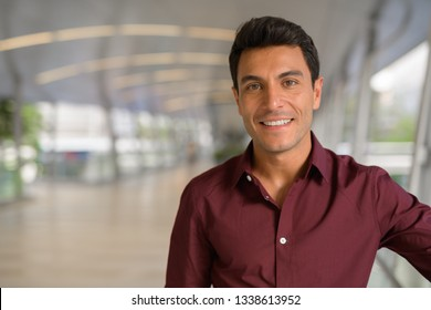 Face of happy Hispanic businessman smiling on the footbridge