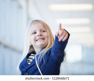 Face of happy little girl in blue jacket pointing at something