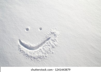Face happy smiley drawn on white snow, frosty winter day. Close-up.
