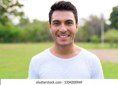 Face of happy young handsome Hispanic man smiling at the park