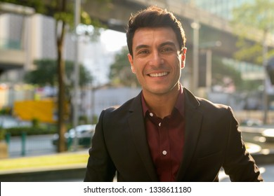 Face of happy young handsome Hispanic businessman smiling outdoors