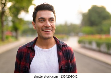 Face of happy young Hispanic hipster man thinking at the park