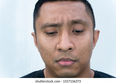 Face of an Indonesian man of Asian heritage on white background who looks ashamed, guilty. He bends his face downward. He wears black-shirt. He is so embarrassed his eyes look at the floor